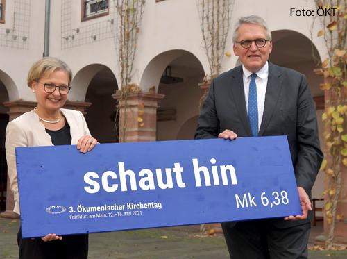 Das Präsidium des Ökumenischen Kirchentags, Bettina Limperg und Thomas Sternberg halten ein Schild hoch, auf dem das Leitwort des Ökumenischen Kirchentags steht: Schaut hin!