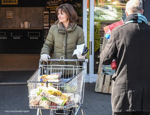 Eine Frau ist unterwegs, um für einen Risikopatienten einzukaufen. Foto: kna/Harald Oppitz