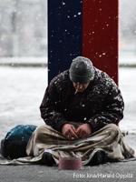 Ein Obdachloser sitzt im Winter auf der Straße. Foto: kna/Harald Oppitz