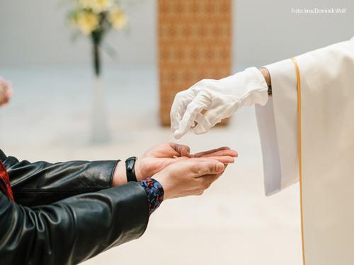 Ein Kaplan spendet die Kommunion. Foto: kna/Dominik Wolf
