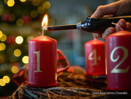 Jemand zündet die Kerzen am Adventskranz an.
