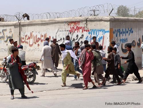 Menschen rennen auf den Flughafen in Kabul zu. Im Hintergrund ist eine Mauer mit Stacheldrahtzaun zu sehen.