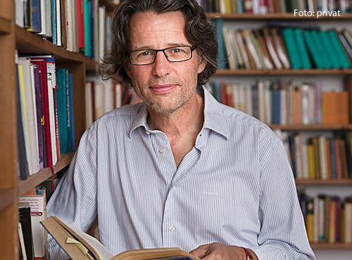 Der Philosoph Albert Kitzler steht in seiner Bibliothek.