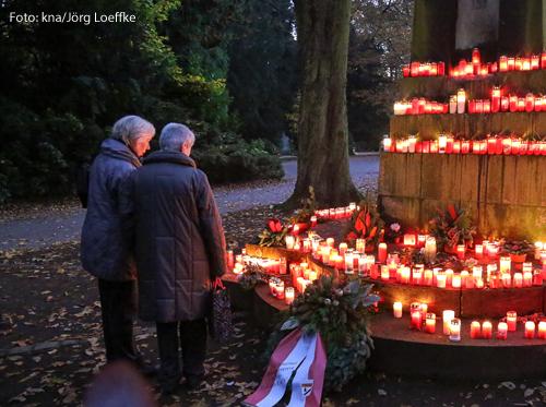 Zwei Frauen stehen vor einem Denkmal mit Kerzen.