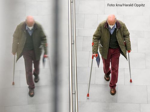Ein alter Mann geht an Krücken einen Gang entlang zu den Impfpunkten im Corona-Impfzentrum in Bonn am 8. Februar 2021. Seine Silhouette spiegelt sich in einer Glaswand.