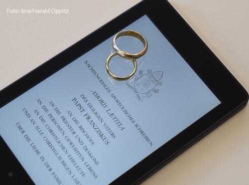 """Auf einem Tablet ist das päpstliche Lehrschreiben """"Amoris laetitia"""" geöffnet. Darüber liegen zwei Eheringe."""