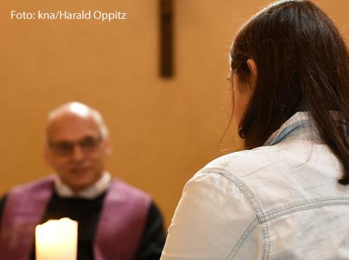 Eine Frau spricht mit einem Priester.