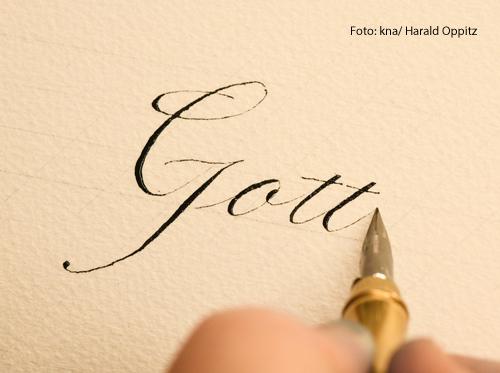 Eine Person schreibt das Wort Gott mit einer Feder auf weißem Papier