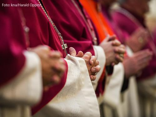 Bischöfe haben die Hände zum Gebet gefaltet.