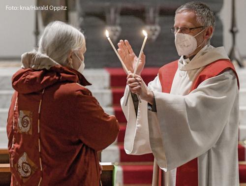 Ein Pfarrer hält zwei Kerzen gekreuzt übereinander und segnet eine Gläubige. Er spendet den traditionellen Blasiussegen.