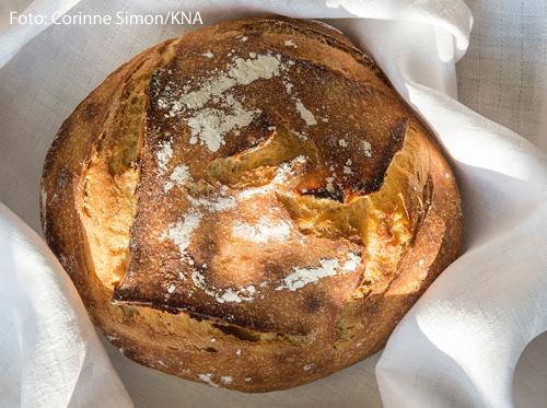 Ein Laib Brot liegt auf einer weißen Tischdecke