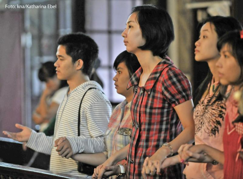 Chinesische Christen stehen in einer Kirchenbank und beten.