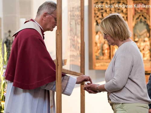Ein Pfarrer teilt einer Frau die Kommunion aus. Er steht hinter einer Plexiglasscheibe.