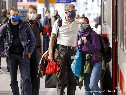 Menschen tragen am Bahnhof Masken