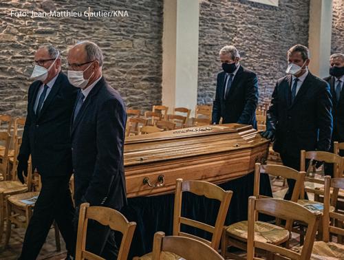 Männer mit Mundschutz tragen einen Sarg in die Kirche zu einer Trauerfeier in Chartres-de-Bretagne