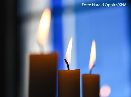 Drei Kerzen brennen vor einem bunten Glasfenster in der Pallottikirche in Vallendar.