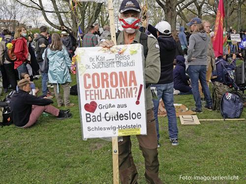 """Ein Demonstrant hält ein Schild, auf dem """"Corona-Fehlalarm?"""" steht."""