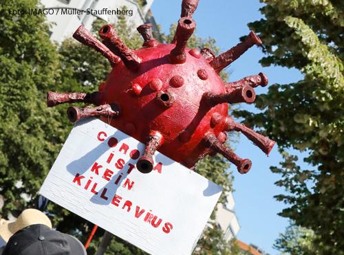 """Ein Mann hält bei einer Demonstration ein Plakat hoch. Darauf steht """"Corona ist kein Killervirus""""."""