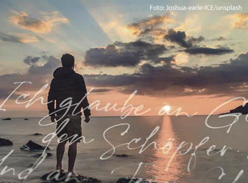 Ein Mann steht am Strand und schaut in den Sonnenuntergang. Über dem Bild sind in weißer Schrift die ersten Zeilen des Credos geschrieben.