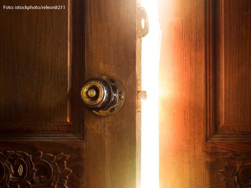 Durch einen Türspalt fällt helles Licht.