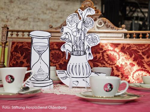 Auf einem Tisch stehen Kaffeetassen und Bilder von Blumenvasen.