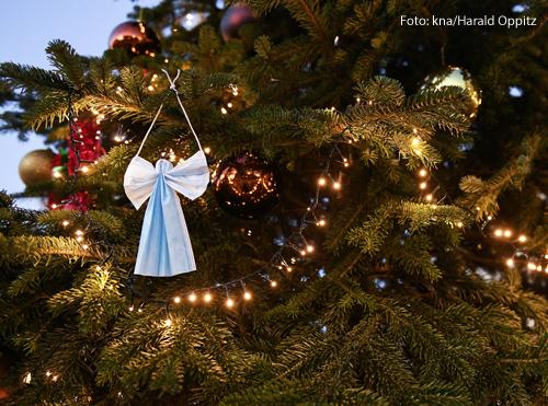 Eine OP-Maske hängt an einem Tannenbaum. Jemand hat sie zu einem Engel gefaltet.