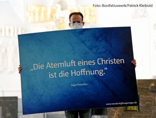 """Ein Mann hält ein Plakat bei der Eröffnung der Diasporaaktion in Würzburg hoch. Darauf steht """"Die Atemluft eines Christen ist die Hoffnung."""""""