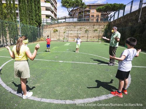 Kinder stehen mit Maske und Abstand auf einem Fußballplatz.