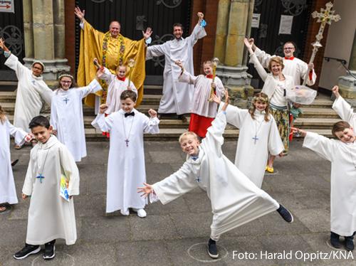 Erstkommunionkinder in weißen Alben posieren für ein Gruppenbild nach der Messe zur Feier der Erstkommunion am 21. Juni 2020 in einer Kirche in Bonn. Auf den Boden sind Kreise gemalt, um den Abstand einzuhalten.