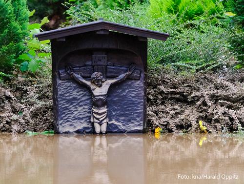 Ein Kreuz ist von braunem Wasser überschwemmt worden und nur noch zur Hälfte zu sehen