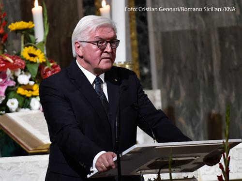 Bundespräsident Frank Walter-Steinmeier hält eine Rede  Im Hintergrund sind Blumen und Kerzen zu sehen.