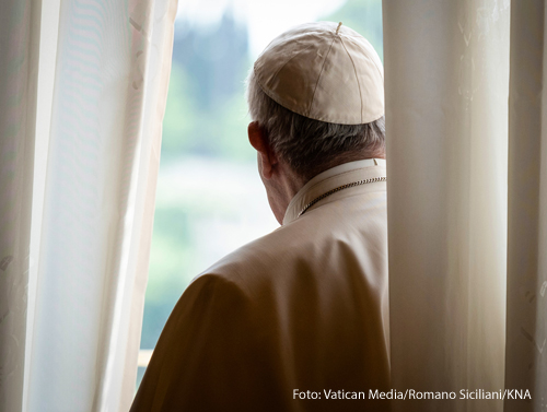 Papst Franziskus steht hinter einem Vorhang und guckt aus einem Fenster im Apostolischen Palast am 20. Mai 2020 im Vatikan.