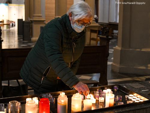 Eine Frau zündet eine Kerze in einer Kirche an.