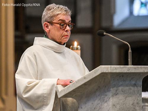 Eine Frau trägt liturgische Kleidung und steht am Ambo in einer Kirche in Bonn