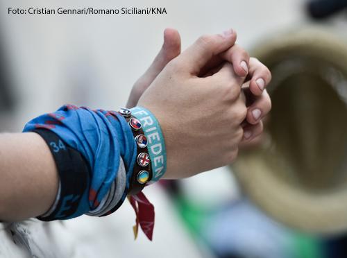 """Betende Hände eines Jugendlichen am 31. Juli 2018 im Vatikan. Am Handgelenk trägt er ein Band mit der Aufschrift """"Frieden""""."""