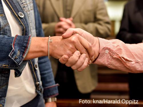 Zwei Menschen geben sich die Hand zum Friedensgruß.