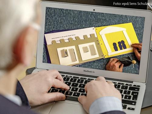 Ein Mann sitzt an einem aufgeklappten Laptop. Im Display ist ein Buch aus Pappe zu sehen.
