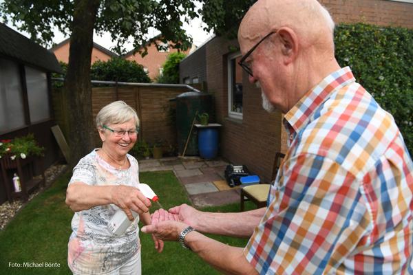 Eine Frau sprüht einem Mann Desinfektionsmittel auf die Hände.