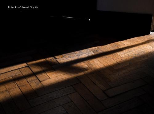 Der Schatten eines Kreuzes fällt durch eine Tür.