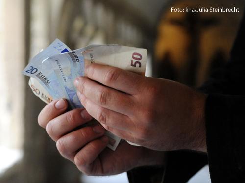 Ein Mann hält Geldscheine in der Hand.