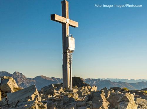 Ein Kreuz auf einem Gipfel vor blauem Himmel
