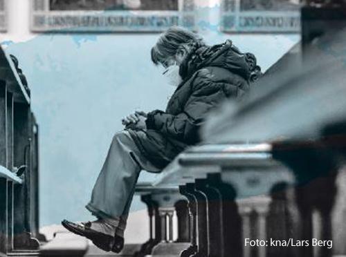 Eine Frau sitzt in einer Kirchenbank.