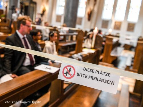 """Auf einem Schild an einer Kirchenbank steht der Hinweis """"Diese Plätze bitte freilassen."""""""