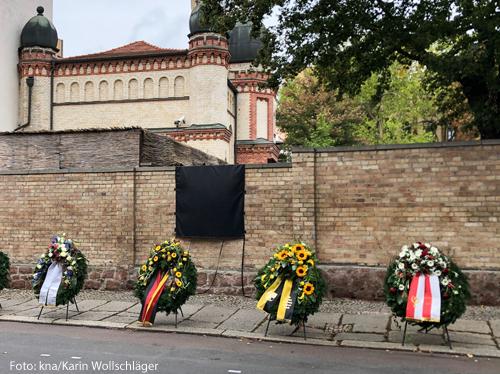 Blumenkränze lehnen an der Mauer der Synagoge in Halle