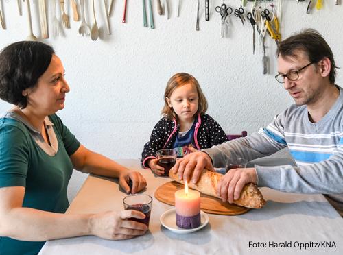 Eine Familie, Vater, Mutter und Tochter, sitzen an einem Küchentisch zusammen. Sie haben Gläser mit Traubensaft und brechen gemeinsam ein Brot.