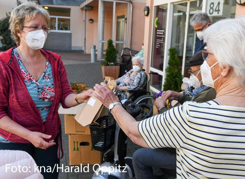Eine Frau verteilt Päckchen vor einem Pflegeheim.