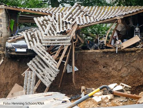 Ein Auto steht unter einem zerstörten Carport in Erftstadt am 16. Juli 2021. Wassermassen haben den Boden am Haus weggeschwemmt.