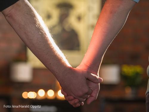 Zwei Männer halten sich vor einem Altar bei der Hand.