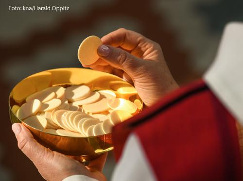 Ein Priester teilt Hostien aus einem goldenen Kelch aus.
