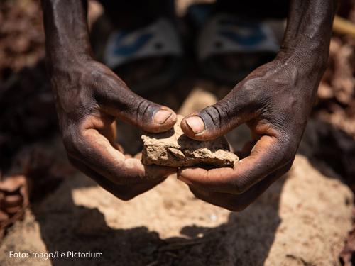 Ein Mann in Afrika zeigt, wie trocken sein Acker durch die Dürre geworden ist.